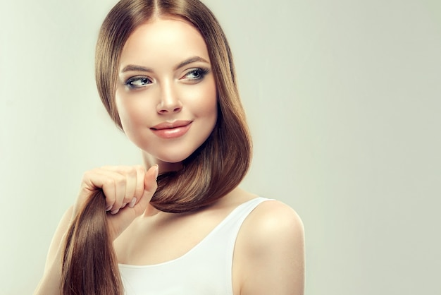 Young, brown haired beautiful model with long, straight hair is holding tail of well groomed and healthy hair in the hand. hair care natural beauty and health.