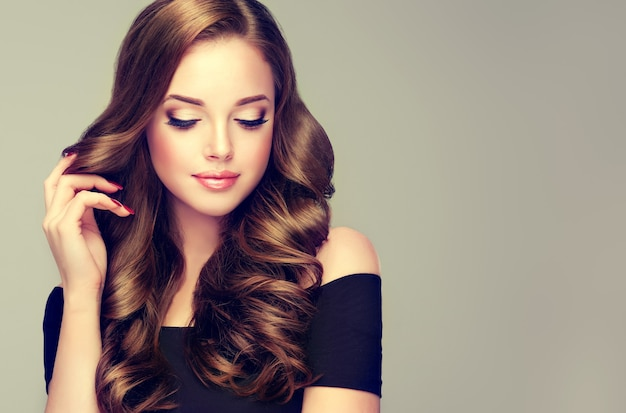 Young, brown haired beautiful woman is tenderly touching long, well groomed hair styled in elegant evening wavy hairstyle. perfect makeup with gilded eyelids and rose lips. hairdressing art and makeup.