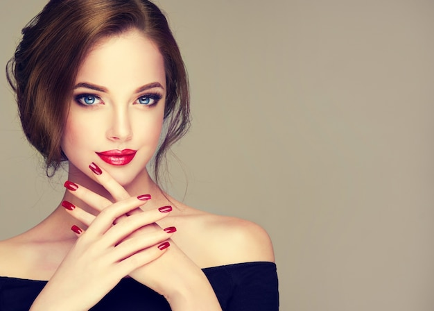 Young, brown haired beautiful woman with long, well groomed hair gathered in elegant evening hairstyle with bright makeup with red lipstick and red manicure on the slender fingers.