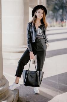革のジャケット、街の遊歩道の黒い帽子の若い茶色の髪の少女