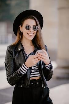 Giovane ragazza dai capelli castani in una giacca di pelle, cappello nero sul lungomare della città e gioca sul telefono cellulare