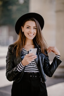 Young brown-haired girl in a leather jacket, black hat on the city promenade posing with mobile phone