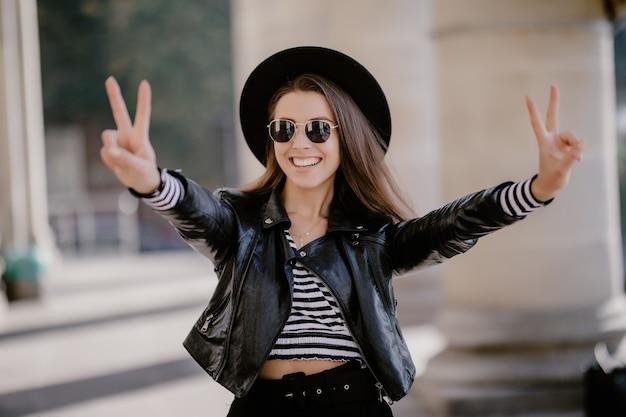 Giovane ragazza dai capelli castani in una giacca di pelle, cappello nero sul lungomare della città