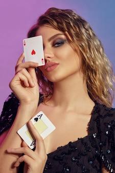 Молодая шатенка с вьющимися волосами, ярким макияжем, в черном блестящем платье держит у лица двух тузов,