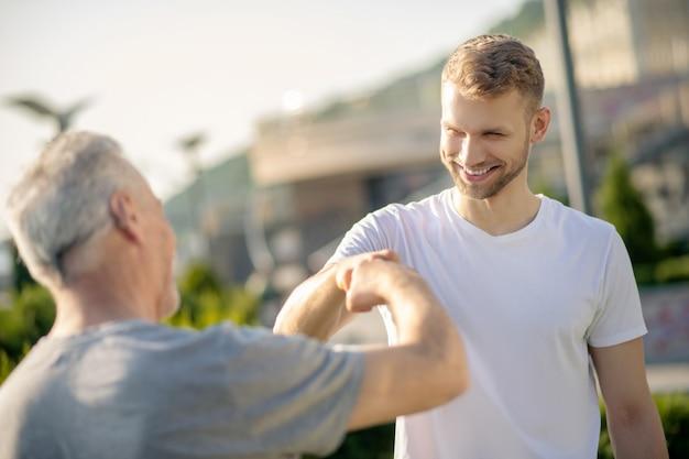 拳に触れる若い茶色の髪の男性と白髪の男性