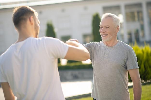 拳に触れる若い茶色の髪の男性と成熟した灰色の髪の男性