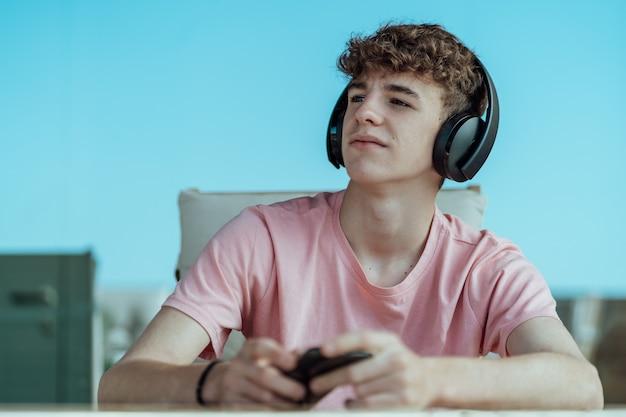 ヘッドフォンとスマートフォンを手に若い茶色の髪のティーンエイジャーの少年