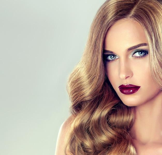エレガントでボリュームのあるイブニングヘアスタイルの若い茶色の髪の女性。長くて濃い巻き毛と赤い口紅の鮮やかなメイクの美しいモデル。理髪アート、ヘアケア、美容製品。