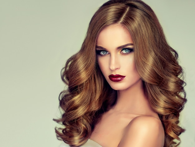 Young, brown haired woman with elegant, voluminous evening hairstyle. beautiful model with long, dense, curly hair and vivid makeup with red lipstick. hairdressing art, hair care and beauty products.