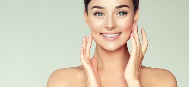 짧고 세련된 헤어 스타일과 깨끗하고 신선한 피부를 가진 젊고 갈색 머리의 여성이 넓은 이빨 미소를 보여줍니다.