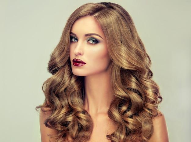 ボリュームのある髪の若い、茶色の髪の女性。長くて濃い巻き毛のヘアスタイルと鮮やかなメイクの美しいモデル。完璧な髪。信じられないほど濃く、波打つ、そして光沢のある髪。