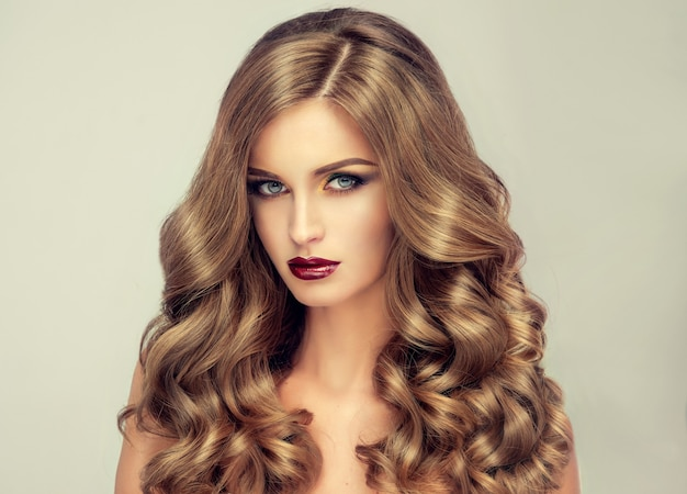 Young, brown haired woman with voluminous hair. beautiful model with long, dense and curly hairstyle and vivid make-up. perfect hair. incredibly dense, wavy,and shiny hair.