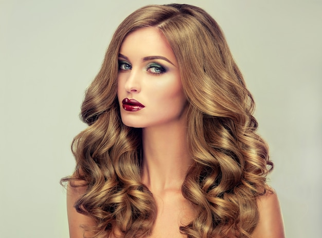 Young, brown haired woman with voluminous hair. beautiful model with long, dense and curly hairstyle and vivid makeup. perfect hair. incredibly dense, wavy,and shiny hair.