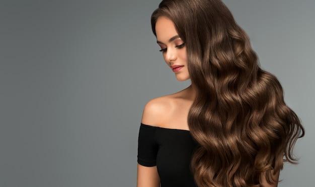 ボリュームのある髪の若い茶色の髪の女性完璧な濃い波状の光沢のある髪理髪アートヘアケアと美容製品