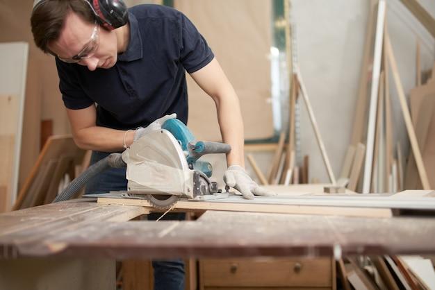 안전 안경과 흰 장갑을 낀 젊은 브루넷은 작업장에서 퍼즐 작업을 한다