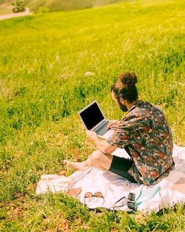 Young brunet man holding laptop on nature
