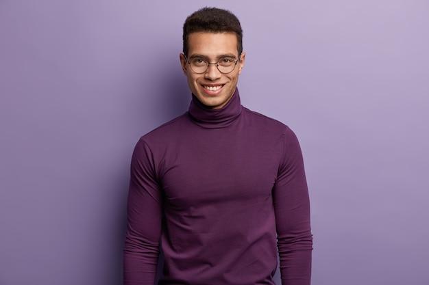 Young brunet man wearing purple turtleneck