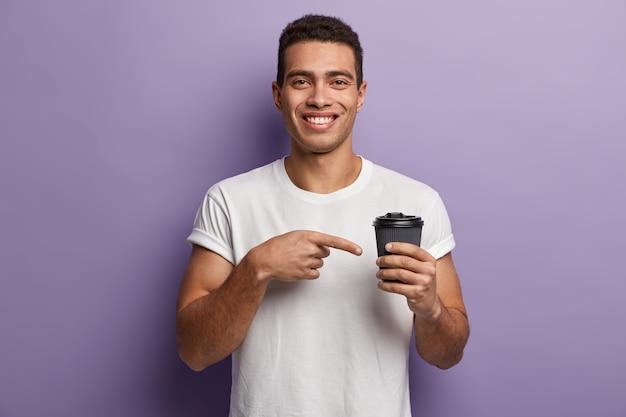 Молодой брюнет в белой футболке, указывая на чашку кофе