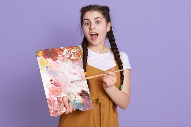 Young brunette artist woman with pigtails holding painter brush and palette over lilac wall, posing with surprise face, standing with opened mouth.