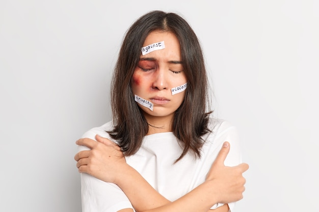 Young brunette asian woman tries to defense herself embraces and keeps hands on shoulders becomes victim of violence beaten by aggressive husband
