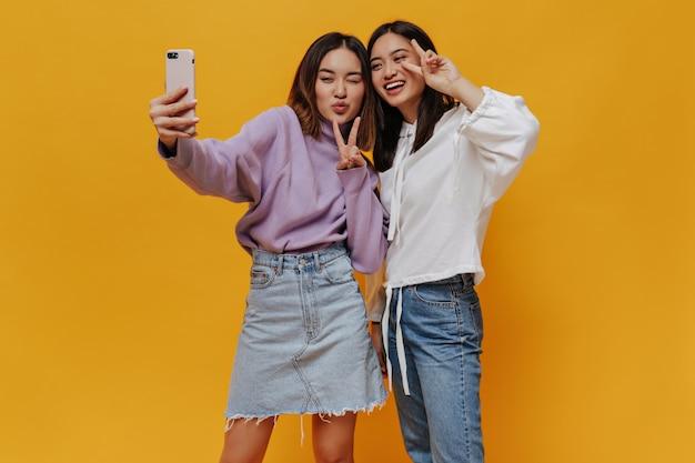 若いブルネットのアジアの女性はオレンジ色の壁に自分撮りをします