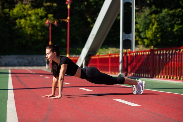 Young brunette athlete model doing plank exercise outdoor at the bridge