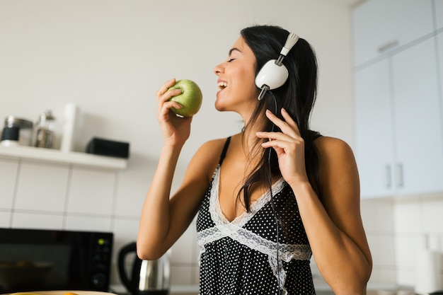 Young brunette attractive woman cooking in kitchen in morning, eating green apple, smiling, happy mood, positive housewife, healthy lifestyle, listening to music on headphones, biting