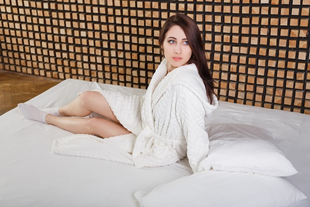 Young brunette beautiful woman sitting on bed at home