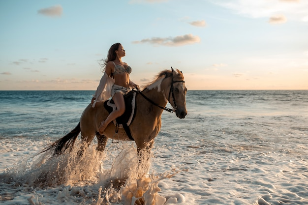 Young brunette beauty having fun with horse and riding on the  tropical beach