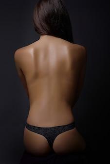 Young brunette beauty nude women back on black