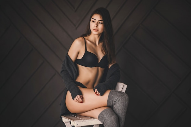 Young brunette in black underwear, knitted knee pads and cardigan sits on a wooden chair