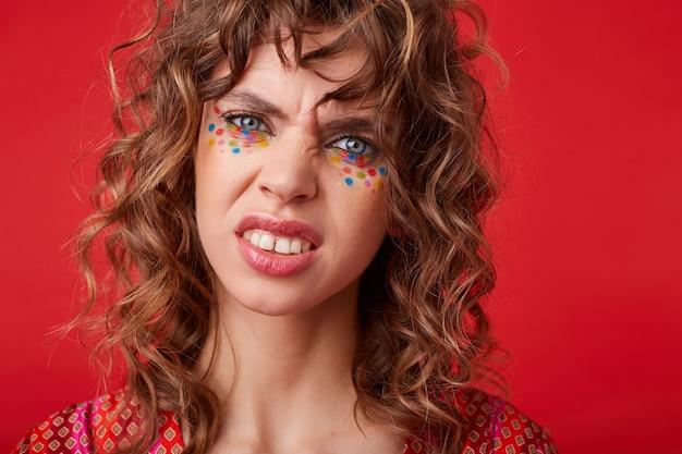 Giovane donna bruna dagli occhi azzurri con acconciatura festosa guardando con il broncio e dimostrando i suoi denti stando in piedi