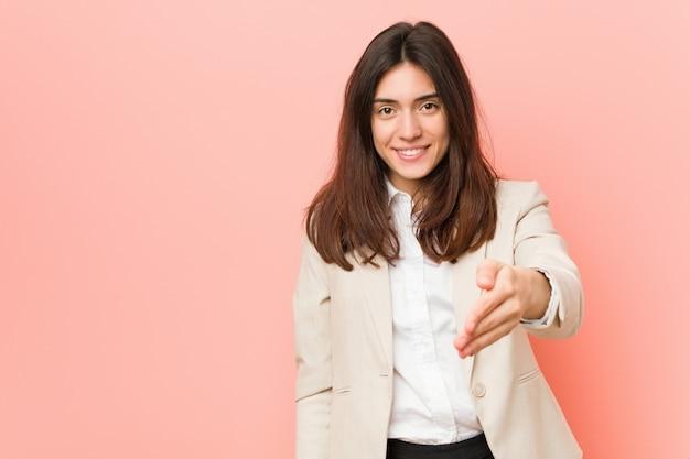 ジェスチャーの挨拶で手を伸ばしてピンクの背景の若いブルネットビジネス女性。