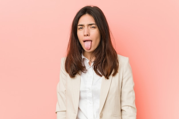 Young brunette business woman against a pink background funny and friendly sticking out tongue.