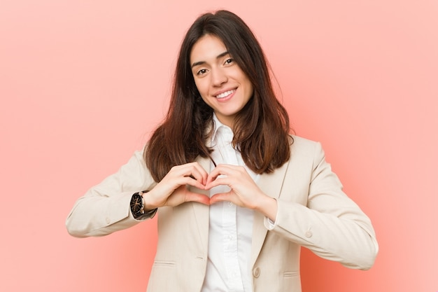 Young brunette business woman against a pink background smiling and showing a heart shape with hands.