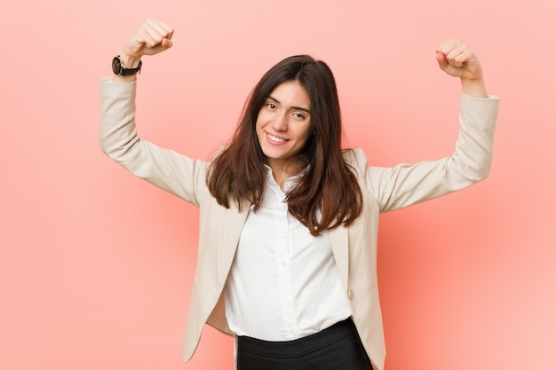 Young brunette business woman against a pink wall showing strength gesture with arms, symbol of feminine power