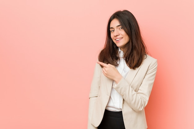 Young brunette business woman against a pink wall smiling and pointing aside, showing something at blank space.