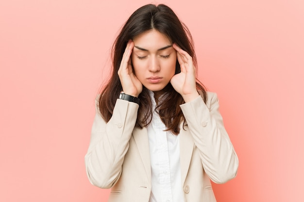 Young brunette business woman against a pink wall touching temples and having headache.
