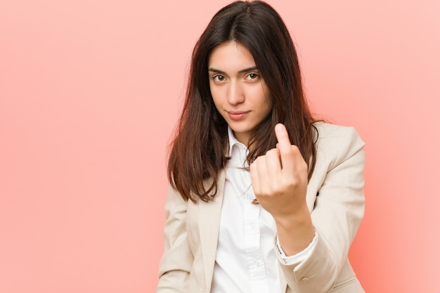 Young brunette business woman againstpink  pointing with finger at you as if inviting come closer.