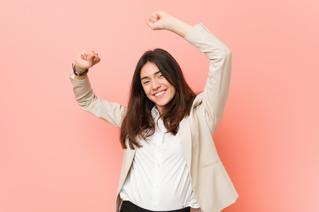 Young brunette business woman celebrating a special day, jumps and raise arms with energy.