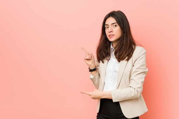 Young brunette business woman shocked pointing with index fingers