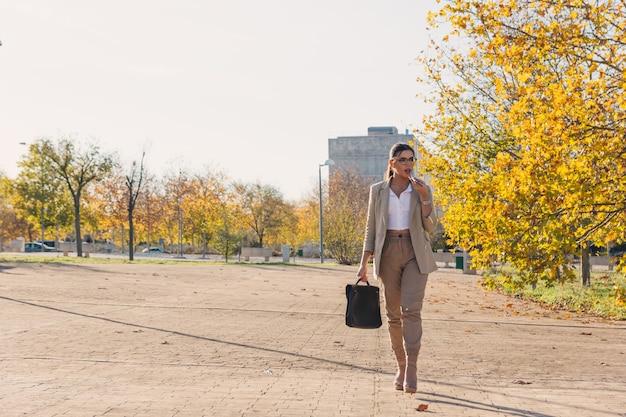 그녀의 서류 가방 및 그녀의 휴대 전화와 함께 걷는 젊은 갈색 머리 비즈니스 여자. 비즈니스 및 기술 개념. 가을 시간.