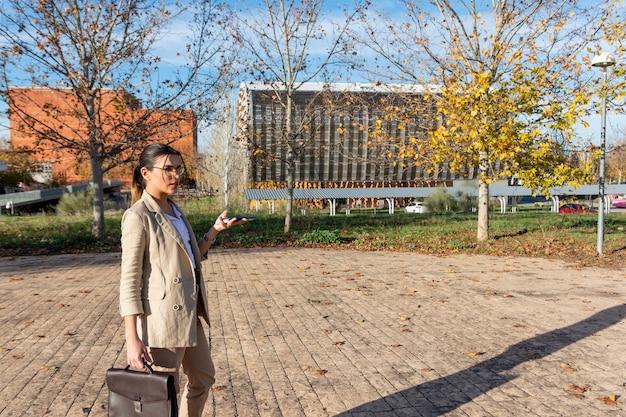 그녀의 서류 가방 및 그녀의 휴대 전화와 함께 걷는 젊은 갈색 머리 비즈니스 여자. 비즈니스 개념.
