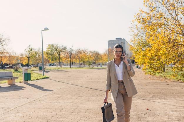 젊은 갈색 머리 비즈니스 여자 그녀의 서류 가방을 걷고 그녀의 휴대 전화로 말하기. 비즈니스 및 기술 개념. 가을 시간.