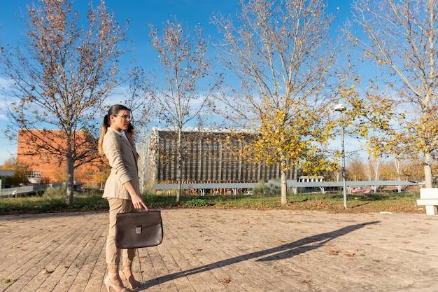 젊은 갈색 머리 비즈니스 여자 그녀의 서류 가방을 걷고 그녀의 휴대 전화를 얘기. 비즈니스 개념.