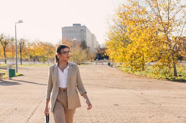 그녀의 서류 가방을 걷고 젊은 갈색 머리 비즈니스 여자. 비즈니스 및 기술 개념. 가을 시간.