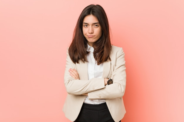 Young brunette businesswoman frowning face in displeasure, keeps arms folded.