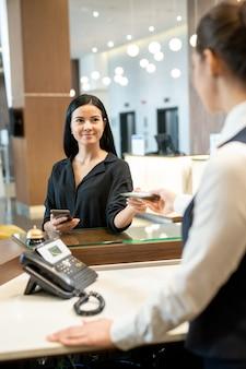 Молодая брюнетка-бизнесвумен в повседневной одежде берет документы из руки портье, стоящего у стойки в холле отеля