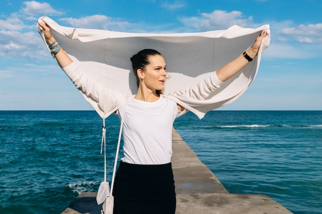 Young brunette in a cardigan and skirt standing on a pier in the background of the sea and enjoys a summer breeze on a sunny day