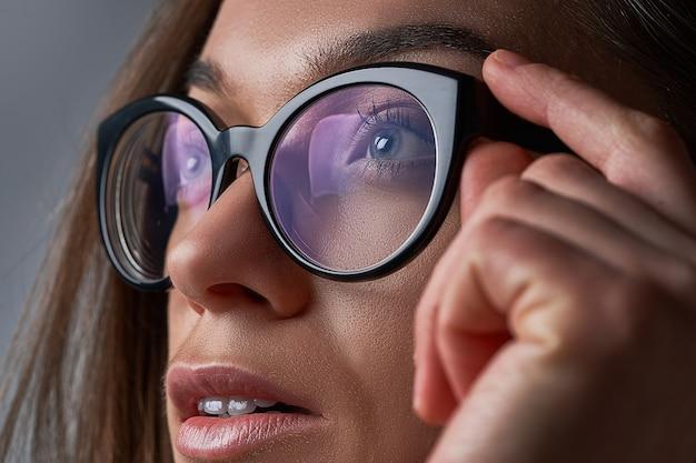 黒いフレームの眼鏡の若いブルネットの白人女性はビジョンのクローズアップ